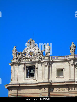 Architectural elements of famous landmark - Saint Peter Basilica fasade baroque style: sculptures, bell and clock on a blue sky background. - Stock Photo