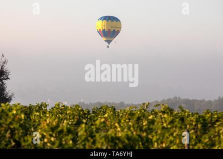 Saint Emilion, France - September 10, 2018: Air balloon flying in the morning over the vineyards near Saint Emilion. Gironde, France - Stock Photo