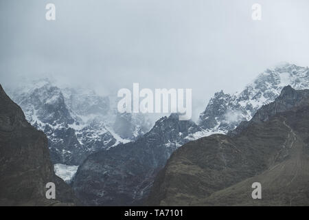 Nature landscape view of clouds and fog covered snow capped Ultar Sar mountain in Karakoram range, Hunza valley. Gilgit Baltistan, Pakistan. - Stock Photo