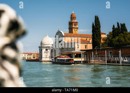 Vaporetto water bus station against San Michele in Isola church with tower in Laguna Nord, Venice - Stock Photo