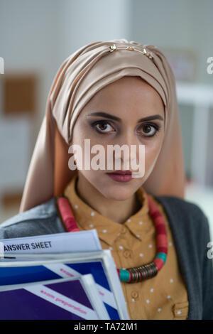 Dark-eyed Muslim teacher holding books standing in school - Stock Photo