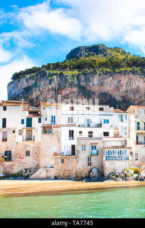 Beautiful traditional houses on the coast of Tyrrhenian sea in Cefalu, Sicily, Italy. Behind the buildings magnificent rock overlooking the bay. The amazing Sicilian city is a popular tourist spot. - Stock Photo