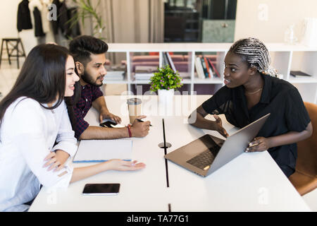 Young female executive presenting her ideas to colleagues in a meeting. Young mixed race people discussing work at desk in office. - Stock Photo