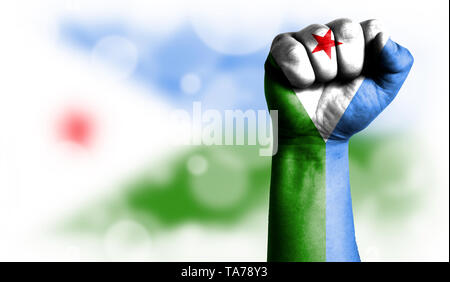 Flag of Djibouti painted on male fist, strength,power,concept of conflict. On a blurred background with a good place for your text. - Stock Photo