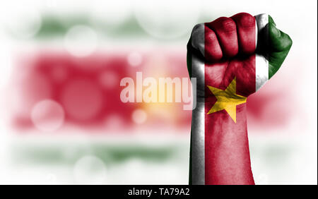 Flag of Suriname painted on male fist, strength,power,concept of conflict. On a blurred background with a good place for your text. - Stock Photo