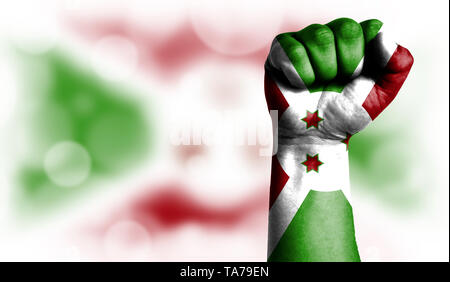 Flag of Burundi painted on male fist, strength,power,concept of conflict. On a blurred background with a good place for your text. - Stock Photo