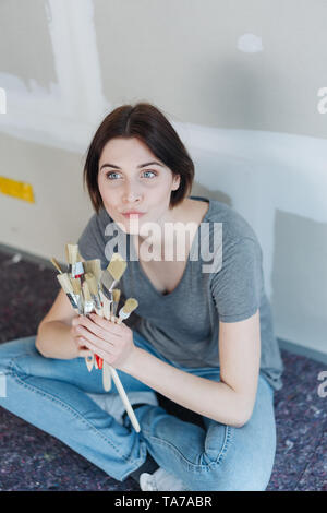 Thoughtful young woman clutching a collection of different paintbrushes in her hands as she sits on the floor in front of an unpainted wall with cladd - Stock Photo