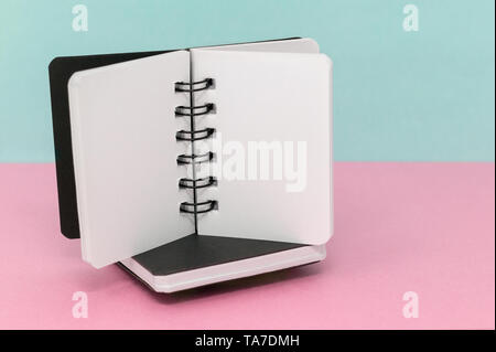 Two notebooks on a pink and blue green background, with space for text - Stock Photo