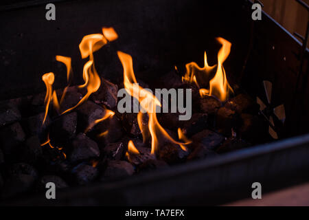 Hot coals in the fire.burning coals in the barbecue, fire in the grill.charcoal preparing for grilling, barbecue grill.Flames and coals of a fire - Stock Photo