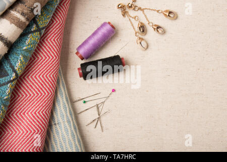 A variety of colourful fabric with assorted sewing pins and thread flat lay image  with copy space for text. - Stock Photo