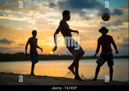 CAIRU, BRAZIL - FEBRUARY, 2018: Young men play an informal game of beach football keepy-uppy in silhouette on the shore of a sunset beach. - Stock Photo