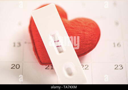 Pregnancy Tests Pregnant woman concept / positive result two lines planning a baby motherhood and healthcare and red heart on calendar background - Stock Photo