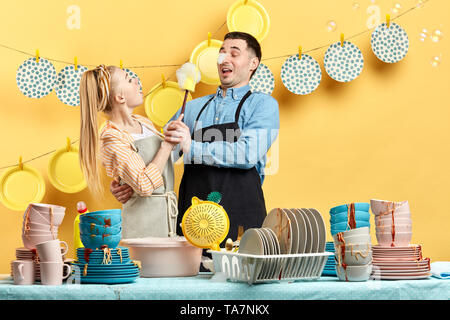funny housewife trying to wash her husband in the kitchen with yellow wall. close up photo. studio shot. - Stock Photo