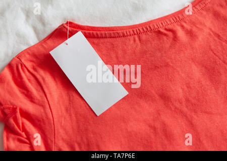 New pink red kid's or women's t-shirt with label on white background. Concept shopping, summer sales, discounts - Stock Photo