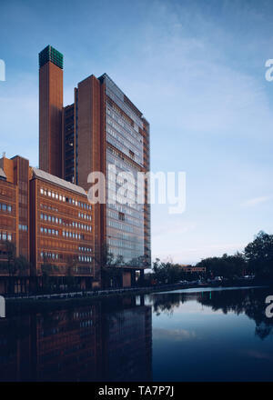BERLIN,GERMANY-25 APRIL,2019: Beautiful sunset in Berlin city.Dusk sun shines and reflects from glass panels on high modern building near the lake in  - Stock Photo