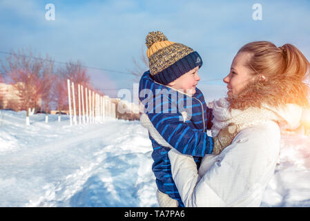 A young mother, a woman with a child, a boy, a son of 3 years old, in the winter outside in warm clothes, playing, having fun, relaxing on weekends in