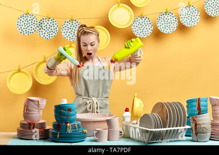 emotional frustrated unhappy woman is scared of bad useless dishwashing liquid. close up photo. feeling and emotion concept. - Stock Photo