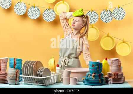 housewife holding her head, having headache, girl having a break, having a rest while washing the dishes in the kitchen with yellow wall, housewife ov - Stock Photo
