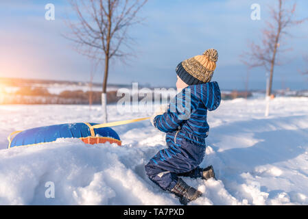 A little boy of 3 years old, in winter on street pulls a tubing, for skiing from a hill, playing having fun relaxing on weekends, background snow - Stock Photo