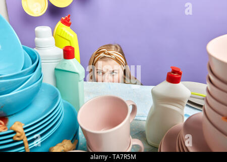 cute lovely beautiful housewife hiding behind the kitchen table, emotional unhapy girl is scared of unwashed dishes - Stock Photo