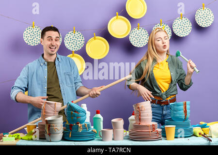 young mad couple having fun in the kitchen with modern interior. studio shot. talent concept - Stock Photo