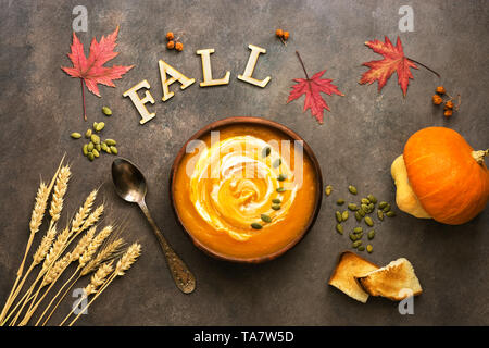 Hot pumpkin soup on an autumn background, maple leaves, ears of wheat. View from above - Stock Photo