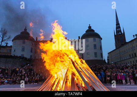 Fire burning & gathered crowds in front of Wrangel Palace celebrating Saint Walpurgis (Mayday eve). Riddarholmen islet, Gamla Stan, Stockholm, Sweden - Stock Photo