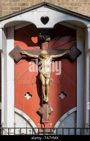 Statue of Jesus christ crucifixion on the side of the Roman Catholic church Our Lady of Mount Carmel and St Simon Stock in Kensington, London - Stock Photo