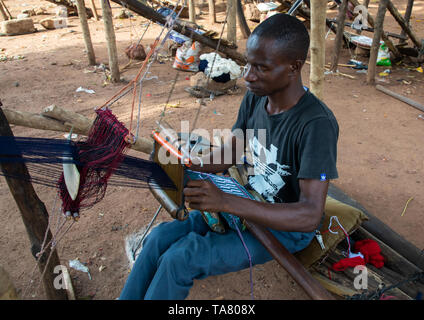 African man from Senufo tribe weaving in a traditional textile factory, Savanes district, Waraniene, Ivory Coast - Stock Photo