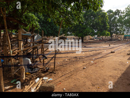 African men weaving in a traditional textile factory, Savanes district, Waraniene, Ivory Coast - Stock Photo