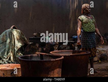 Senufo woman prepairing shea butter in a traditional karité factory, Savanes district, Tcheregnimin, Ivory Coast - Stock Photo