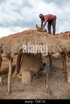 Senufo blacksmith putting charcoal from the top of the house, Poro region, Koni, Ivory Coast - Stock Photo