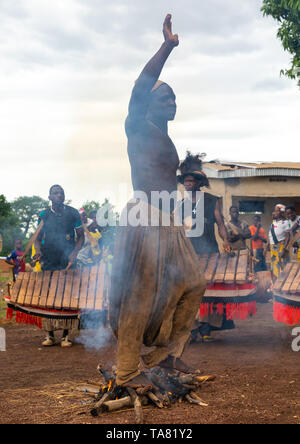 Shirtless man walking in the fire during the Ngoro dance, Savanes district, Ndara, Ivory Coast - Stock Photo