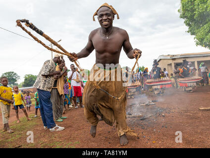 Young Senufo shirtless man dancing the Ngoro with a whip during a ceremony, Savanes district, Ndara, Ivory Coast - Stock Photo