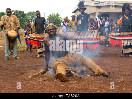 Shirtless man sitting in the fire during the Ngoro dance, Savanes district, Ndara, Ivory Coast - Stock Photo