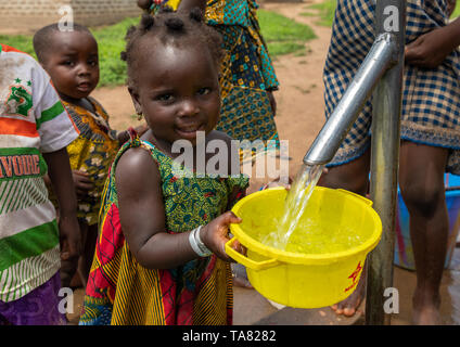 African children collecting water from a well with a pump, Bafing, Yo, Ivory Coast - Stock Photo