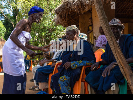Senior Dan tribe woman begging for money to the chiefs during a ceremony, Bafing, Gboni, Ivory Coast - Stock Photo