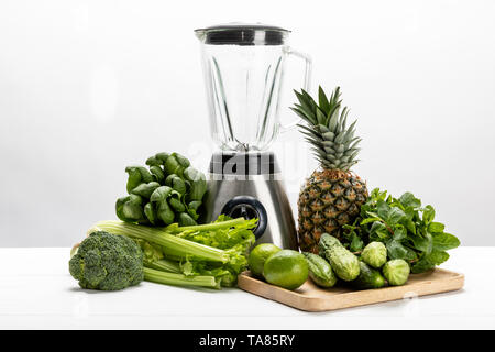 green fresh spinach leaves near organic celery, cucumbers, broccoli fruits and blender on white - Stock Photo