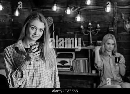 Friends on relaxed faces in plaid clothes relaxing, defocused. Girls relaxing and drinking mulled wine. Rest and relax concept. Friends enjoy mulled wine in warm atmosphere, wooden interior. - Stock Photo