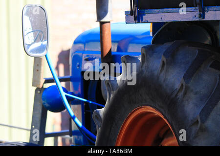 Close up of big tire of blue old ancient  antique tractor with rear view mirror and engine on a farm in Netherlands - Stock Photo