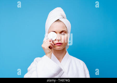 Photo of young woman in white coat and towel on her head with cotton pad in hand on empty blue background - Stock Photo