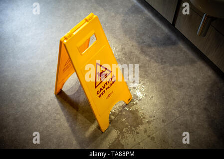 Caution wet floor safety stand up yellow warning sign in a toilet. - Stock Photo
