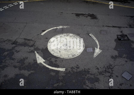 An aerial view of a painted road arrowed roundabout with no cars on could be used for analogy or concept image of being confused or lost etc. - Stock Photo