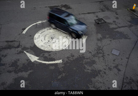 Aerial view of a painted arrowed roundabout with a single car going around. Could be used as an analogy or concept as being lost or going in circles. - Stock Photo