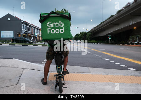 A Grab Food cycle rider on the streets of Singapore delivering food waiting at a crossing of a busy road as a rain storm moves in for a dramatic image. - Stock Photo