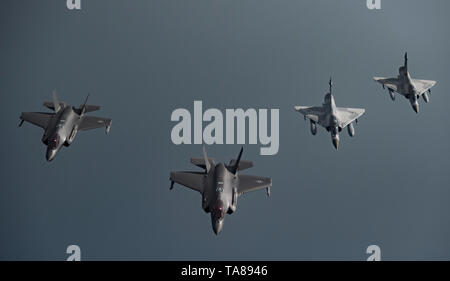 Qatar Emiri Air Force Mirage 2000 fighter jets, right alongside U.S. F-35A Lightning II stealth fighters in formation during an escort patrol May 21, 2019 over Qatar. The joint patrol is part of the expanded military operations in the middle east to counter a perceived threat from Iran. - Stock Photo