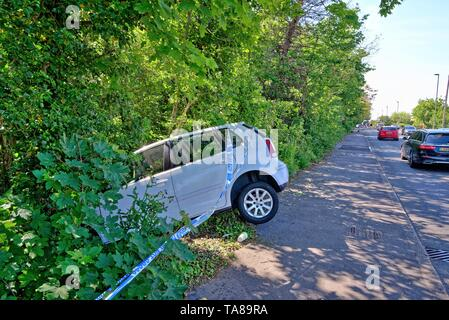 A white saloon car face down in a ditch after crashing off a main road, Shepperton Surrey England UK - Stock Photo