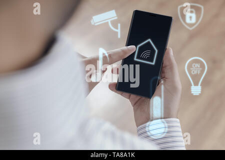 Man using smartphone to control Smart home - Smart house concept - Stock Photo