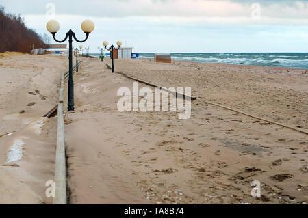 sand-covered promenade, sea promenade after storm, Yantarny village, Kaliningrad region, Russia, January 20, 2019 - Stock Photo
