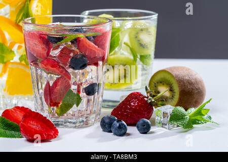 Various colorful smoothies or juices in bottles and ingredients on dark. Healthy diet detox vegan clean food concept, top view. - Stock Photo